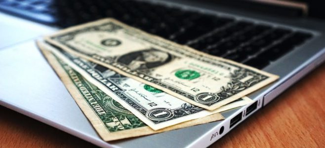 Image of money laid on a laptop