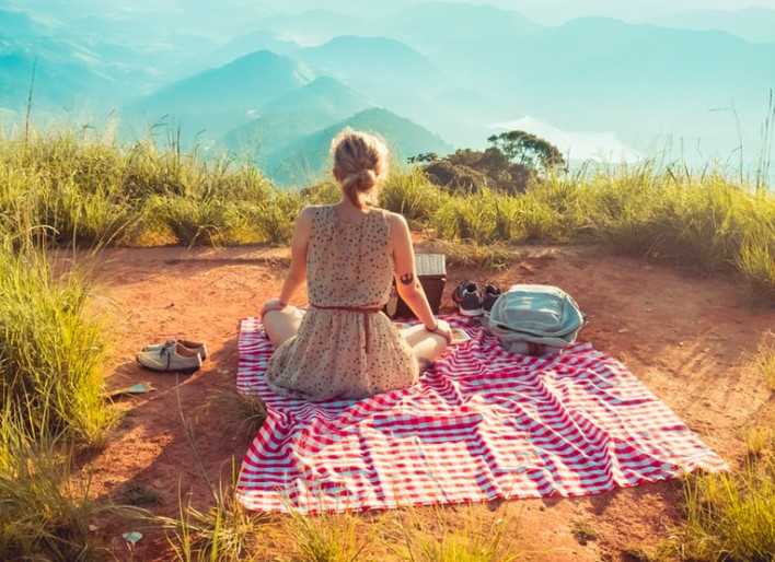 Image of a woman on blanket with picnic items