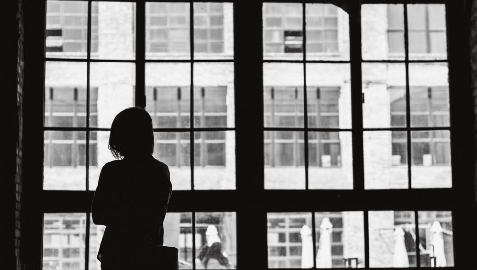Image of woman looking out the window for her apartment
